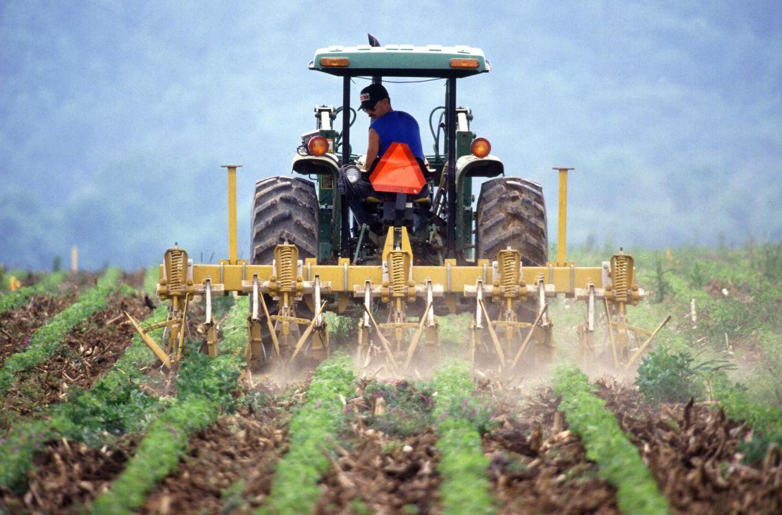 Farmer_and_tractor_tilling_soil.jpg